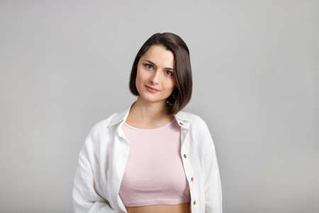 High key calm portrait of young brunette mixed race woman in pink tank and white shirt looking at camera.