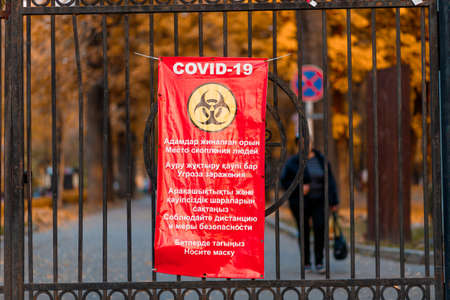 Almaty, Qazaqstan - May, 02, 2021: Banner on street gates with COVID-19 and restrictive measures, risk zone. Editorial
