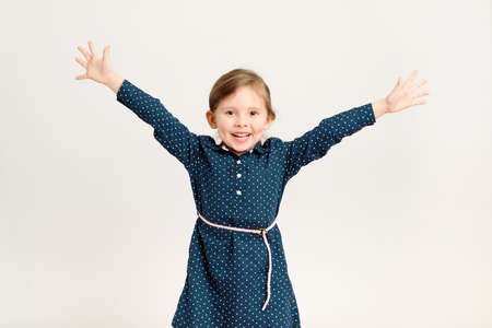 Happy little girl 4-6 years old wearing a blue dress with polka dots raised her hands in different directions, standing on a white background. Freedom, joy, school holidays
