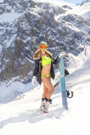 Caucasian fitness cute young model posing in swimwear on a snowboarding slope, winter time, copy space