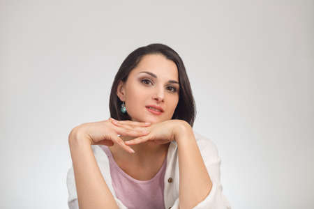 High-key studio portrait of a young brunette multiethnic woman in light clothes looking at camera. Standard-Bild