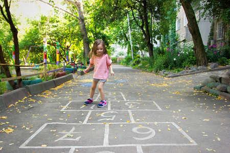 Little cute girl 4 yo playing hopscotch on playground outdoors. Lifestyle kid portrait outdoor. Standard-Bild