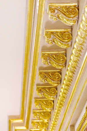 Close-up decorative gold stucco ceiling fillet on the ceiling in luxurious expensive interior of a large baroque royal living room. antique molding, gold trim. Vertical