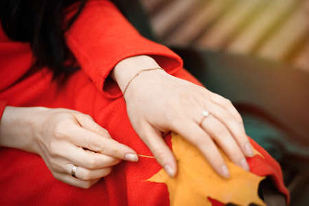 Close-up female hands with bracelet and rings with yellow autumn leaf on the knees.