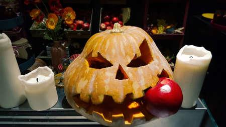 Standard symbol of Halloween, Jack lantern. Scary head of pumpkin bites red apple. Festive decoration Standard-Bild