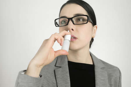 Young woman in glasses, using nasal spray