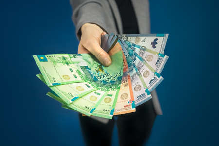 Close-up of tenge in womans hand on blue background. Selective focus