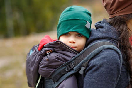 A happy boy travels behind his mother in a baby carrier