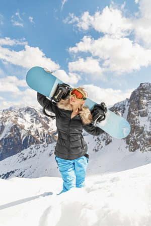 Beautiful young woman holding snowboard on her shoulders. Snowboarder or snowboarding concept at sunny day