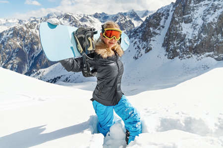 Portrait of beautiful snowboarder female going to freeride in winter mountain high. Sunny winter holiday, winter sport Standard-Bild