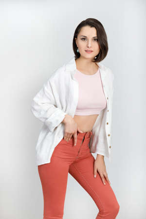 Cute brunette woman 30s in coral jeans, pink tank top and white shirt on white background. High key vertical shot