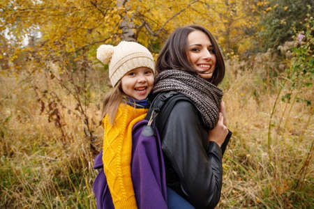 Happy young mother with her kid girl on back in ergonomic baby carrier in autumn nature. Babywearing concept