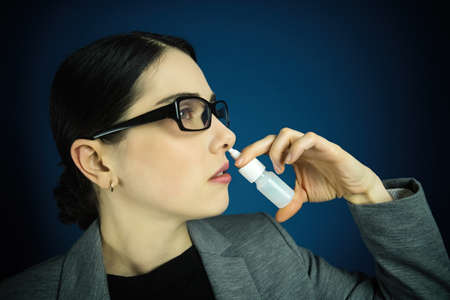 Young woman in glasses, using nose spray on blue background