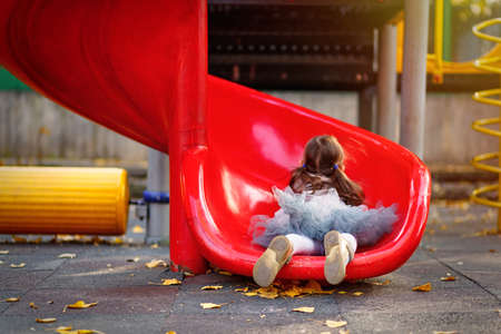 A cute girl in skirt tutu is riding a playground slide. Lifestyle outdoor portrait of a child.