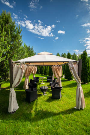 White canvas gazebo with plastic garden furniture in a summer green lawn. Vertical, copy space