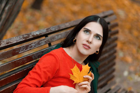 Young woman 25-35 years old sits on a bench in autumn park with big yellow leaf in hands and looks into the sky