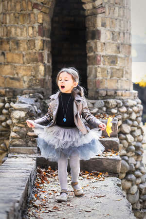 Little cute girl in fashionable autumn clothes sings on the background of a stone castle like a fairy princess