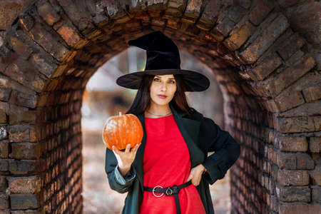 Beautiful young woman portrait in witch hat, holding a orange pumpkin. Halloween mood