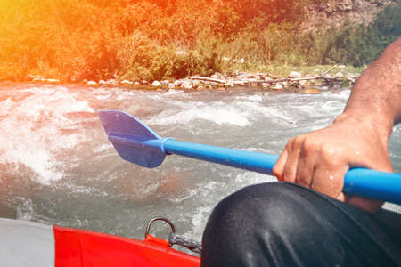 Paddle in hand on the edge of a raft rafting down a mountain river. Standard-Bild