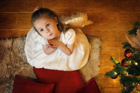 Cute blond angel girl wearing white dress 3-5 years old sitting on the carpet near the New Year tree. Top view. Selective soft focus, film grain effect