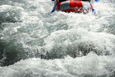 Rapid rapids of a mountain river with rafting tourists in an inflatable raft with copy space.
