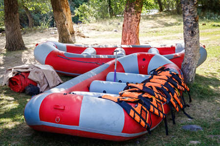 Inflatable rafting boats with equipment stand on the shore in full readiness.