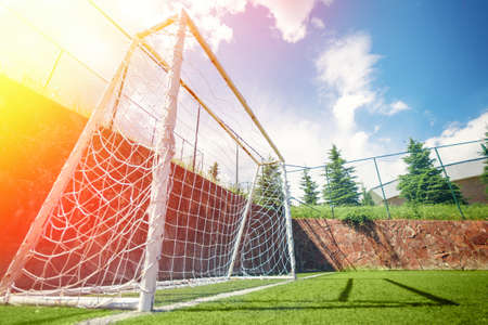 Football or soccer goal on an amateur small field, lens flare and blue sky Standard-Bild