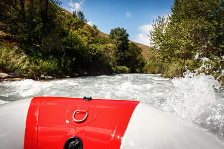 Foam and spray around the paddle in hand on the edge of a raft rafting down a mountain river.