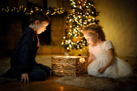 Children opened a magical New Years gift in a Christmas interior with a Christmas tree and garlands. Selective soft focus, film grain effect