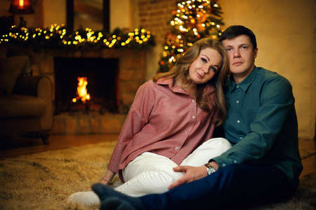 Beautiful middle aged caucasian couple posing in christmas interior with a christmas tree and garlands. Selective soft focus, film grain effect Standard-Bild