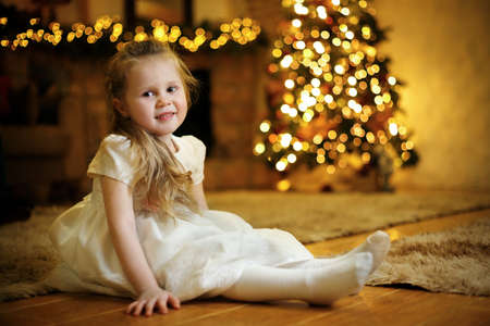 Portrait of a blond cute girl 3-5 years old sitting on the floor against the background of a festive Christmas tree. Selective soft focus, film grain effect Standard-Bild