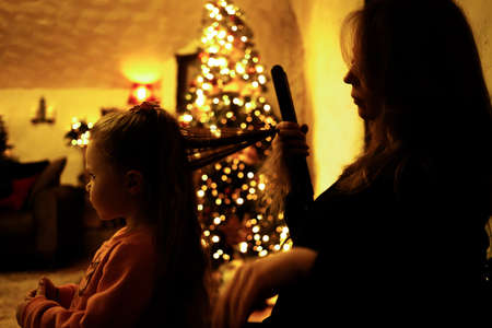Mom combing her daughter for a festive dinner in the room with a christmas tree. Selective soft focus, film grain effect