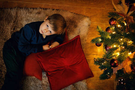 A blond boy 5-7 years old lies on the carpet near the New Year tree, looking at the camera. Top view. Selective soft focus, film grain effect