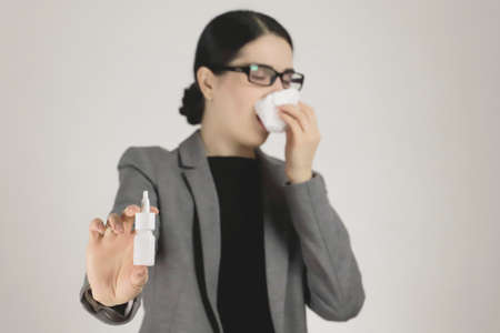 Allergy in a young woman in a gray jacket and glasses. Allergy nasal spray in hand. Selective focus. Standard-Bild