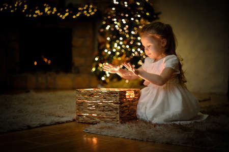Little girl weared in white dress opened a magical New Years gift in a Christmas interior with a Christmas tree and garlands. Selective soft focus, film grain effect