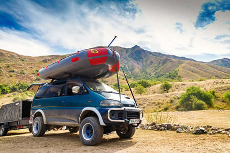 Almaty, Kazakhstan - August 04, 2021: Rafting boat on the roof of a Mitsubishi Delica car on mountainous terrain