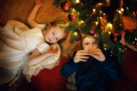 Brother and sister lies on the carpet near the New Year tree in cozy christmas interior with festive garland. Selective soft focus, film grain effect