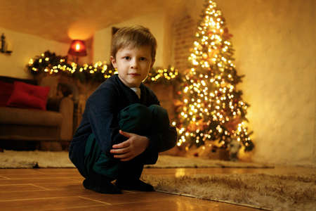 A boy sits on the floor in a festive room on the eve of the new year, decorated with a christmas tree and garlands. Selective soft focus, film grain effect