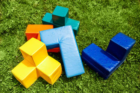 Big colorful tetris cubes on green grass. Outdoor team building games. Top view