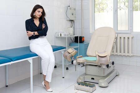 Sad young woman in front of gynecological chair at clinic.