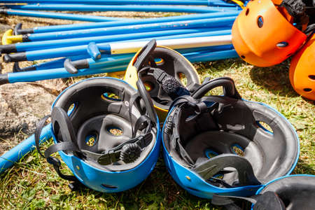 Preparation of protective equipment for rafting. Helmets and paddles lie on the ground. Standard-Bild