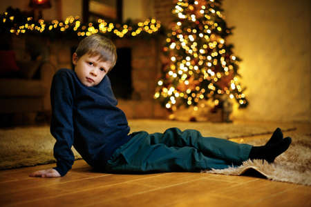 Portrait of a blond cute boy 5-7 years old sitting on the floor against the background of a festive Christmas tree. Selective soft focus, film grain effect