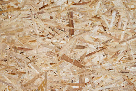Pressed wooden shavings panel background, texture of oriented strand board, OSB.