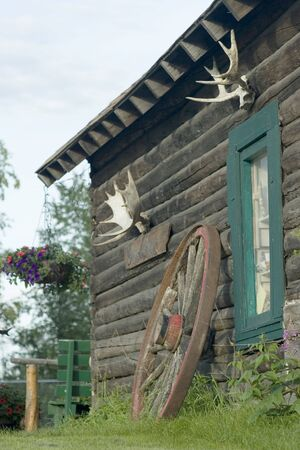 Old alaskan log cabin with antlers and wheel as decorations.