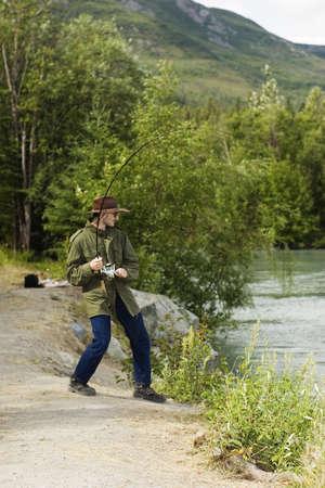 Fisherman playing big salmon - chinook or king salmon