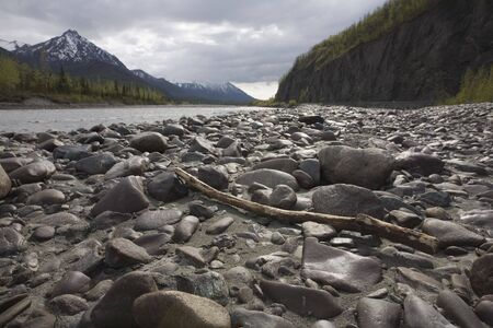 Wide-angle landscape shot of the gravel bar next to river in Alaska