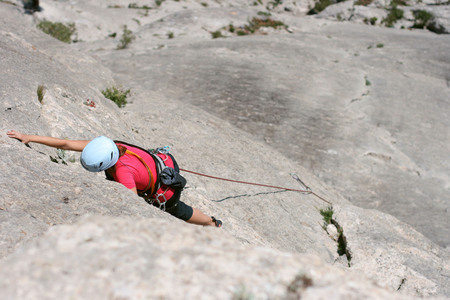 rock climbing: Climber girl in a red hat  climbs on rock