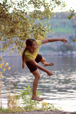 slack: girl walks on Slacklining on the background of the river and the trees Stock Photo