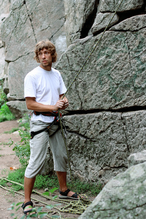 Man ensures the safety of climber man with ropes and devices Stock Photo