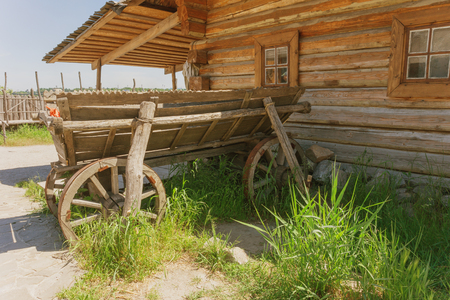old wood farm wagon: old cart near the house of logs